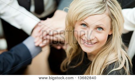 High view of people with hands together and a businesswoman smiling at the camera. Concept of union in business