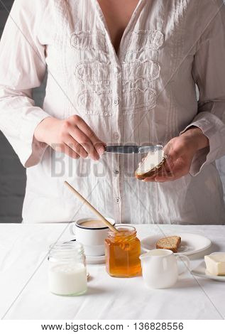 Healthy eating. Young girl preparing healthy breakfast with honey, yogurt and buttered rusk