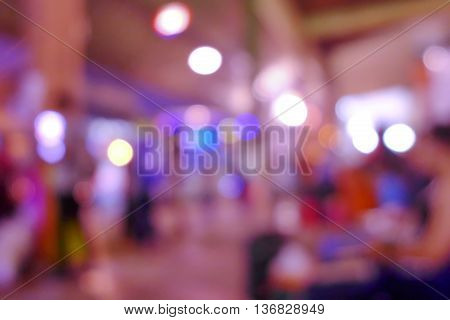 Abstract blurred image of people in night exhibition. cool light tone.