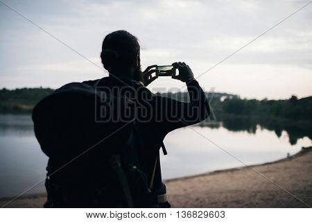 Silhouette Of Hiker Taking Pictures Of Lake With Smartphone