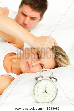 Attractive man and angry woman in bed looking at the alarm clock going off