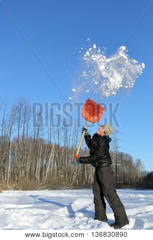 boy in clearing in winter woods vigorously tosses snow shovel