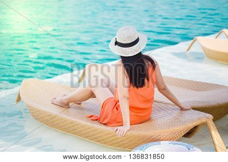 Woman relaxing in deck chair by the pool
