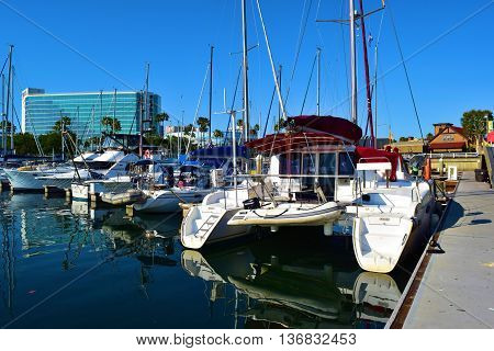 June 15, 2016 in Long Beach, CA:  Catamaran, sail boats, and yachts docked in the Long Beach Harbor at Shoreline Village where locals and tourists shop at the retail stores and restaurants taken in Long Beach, CA