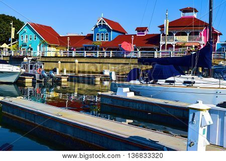 June 15, 2016 in Long Beach, CA:  Sail Boats and yachts docked at Long Beach Harbor with the colorful buildings of Shoreline Village beyond which has retail shops and restaurants where locals and tourists enjoy shopping and dining taken in Long Beach, CA
