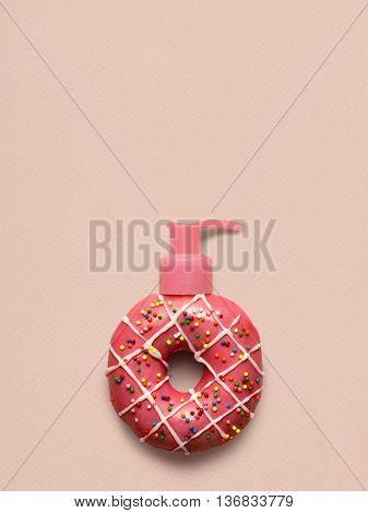 Creative still life of a tasty sweet strawberry donut with a cosmetic pump dispenser on pink background.