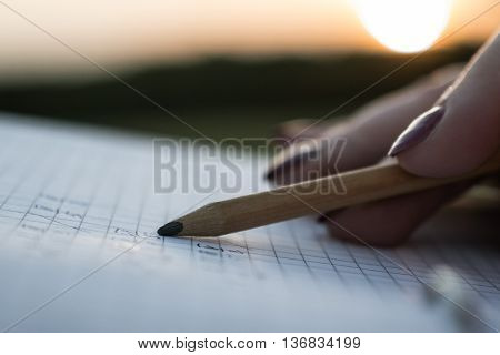 a notebook and pencil close up in the hands of a sunset and a young girl writes in a notebook a pencil of solar light falls on a notebook