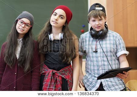 boy and two girls with headphones and tablet posing for camera on background of green blackboard in classroom