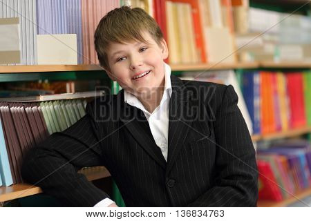 pupil wearing jacket in school library rested on shelf of bookcase looking at camera