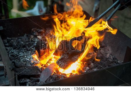 heating the metal strand in the coals before forging