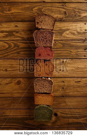 Many mixed alternative baked breads presented as samples for sale in line on rustic wooden table in professional bakery: pistachio, beetroot, tomatoes, lavender, sea salt, coal, sweet potato