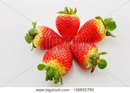 Closeup of not fully ripe strawberries. Over white background