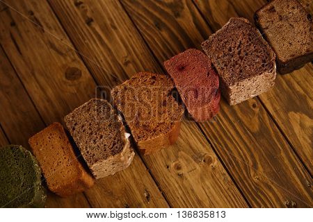 Many mixed alternative baked breads presented as samples for sale in line on rustic wooden table in professional bakery: pistachio, beetroot, tomatoes, lavender, sea salt, coal, sweet potato Side view