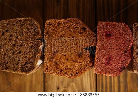 Many mixed alternative baked breads presented as samples for sale in line on rustic wooden table in professional bakery: pistachio, beetroot, tomatoes, lavender, sea salt, coal, sweet potato Close view