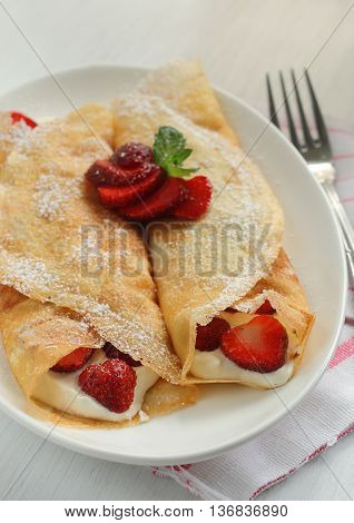 Crepes with strawberry jam and a cream.