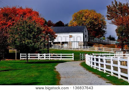 Lancaster Pennslvania - October 18 2015: White fences pathways trees with Autumn foliage and the Old Farm Equipment Shed / Corn Barn at the Amish Farm and House Museum *