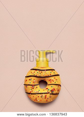 Creative still life of a tasty sweet yellow donut with a cosmetic pump dispenser on pink background.