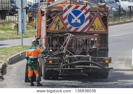 Road worker carries out repairs to the road using a special truck fills holes with bitumen