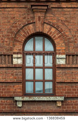 Window with an arch on the background wall of brown brick. From the series window of Saint-Petersburg.