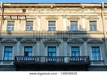 Facade of classic house with windows and a balcony.