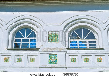 Windows with colorful ancient mosaic tiles in Nicholas Vyazhischsky stauropegic monastery Veliky Novgorod Russia. Architecture view with decorative architecture details