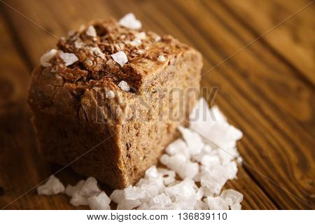 Very close focus on healthy alternative baked bread with crunchy crust covered with sea salt, all presented on wooden table