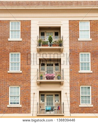Apartment building extior wall red brick symmetrical architecture with windows and balcomies in three.
