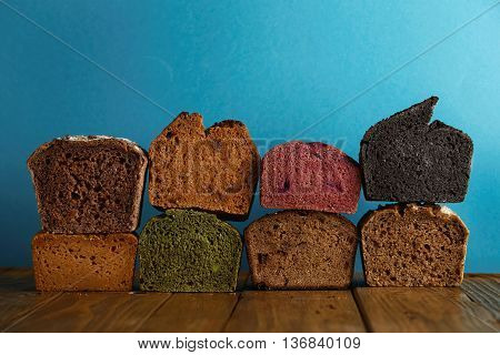 Many mixed alternative baked breads presented as samples for sale on blue background in professional bakery: pistachio, beetroot, tomatoes, lavender, sea salt, coal, sweet potato