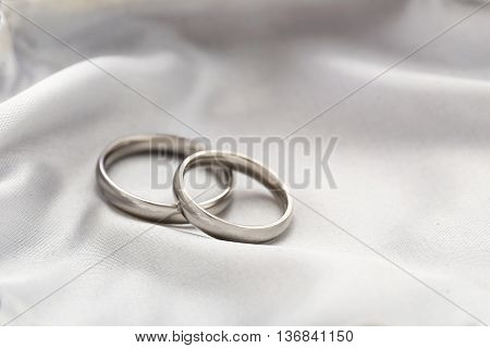 Silver wedding rings on a white satin