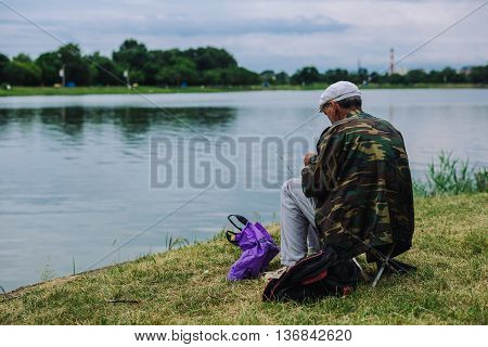 ARMAVIR, RUSSIA - JULE 02, 2016: Man sits on the shore of the lake and catches a fish on a bait on a summer day