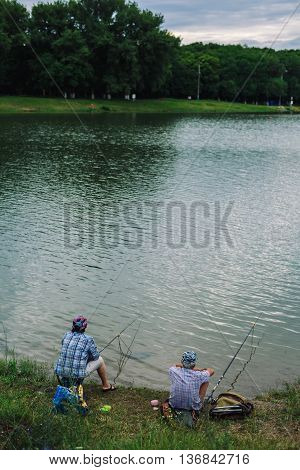 ARMAVIR, RUSSIA - JULE 02, 2016: Couple sits on the shore of the lake and catches fish with a fishing rod on a summer evening