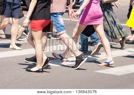 legs of pedestrians crossing the road on summer day