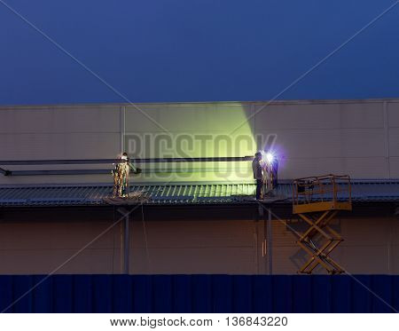 Worker Welding Metal Parts Of Building