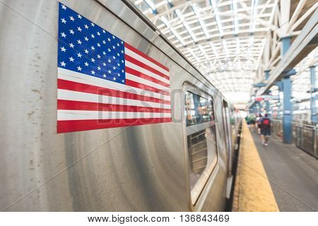 United States flag on a subway train in New York. There are some unrecognizable and blurred persons on the platform waiting to board. Transport and travel concepts. Focus on the flag