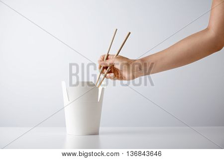 Woman hand uses chopsticks to pick up tasty noodles from takeaway blank box isolated on white Retail set presentation