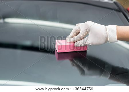 Car detailing series : Closeup of hand waxing windshield