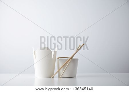 Opened and closed takeaway boxes for chinese noodles presented with chopsticks, isolated on white Retail set