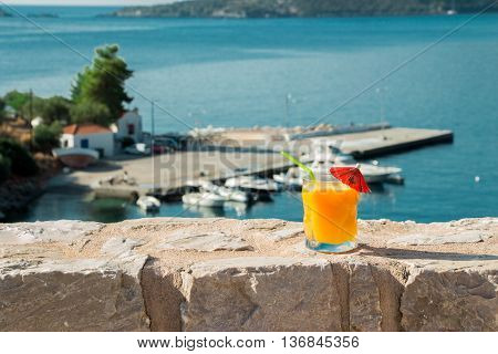 Right a glass of orange juice on the background the sea and the sea berth. Orange juice grass with sea views. Horizontal. Daylight.