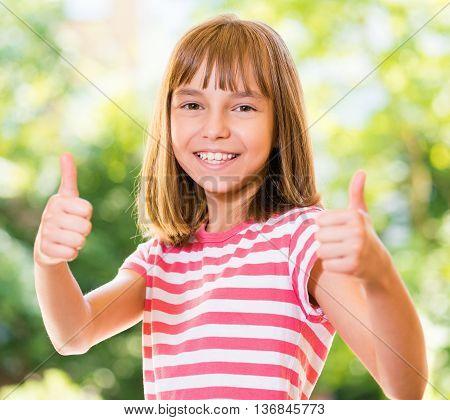 Portrait of happy girl 10-11 year old showing thumbs up gesture. Beautiful schoolgirl posing outdoors.