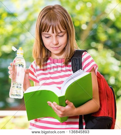 Outdoor portrait of happy girl 10-11 year old with book, schoolbag and bottle of fresh. Back to school concept.