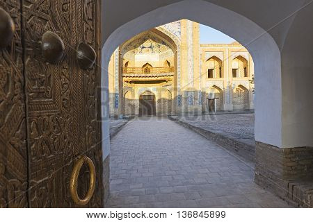 Carved wooden door's brass knocker and archway.