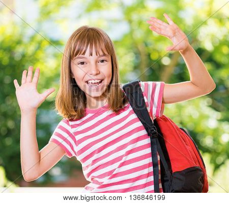 Cheerful cute girl 10-11 year old posing at park. Happy pupil with backpack.