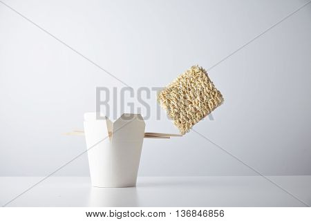 Brick of dry noodles balances on the edge of chopsticks on blank takeaway box isolated on white commercial retail set mockup