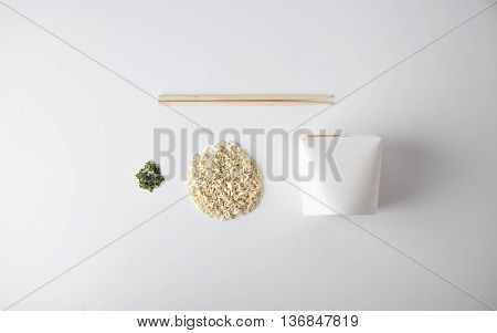 Commercial retail set of takeaway noodles business: blank box, dry pasta in circle shape, chopstiks and spices isolated on white top view