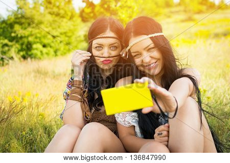 Two cute cheerful sisters in boho hippie outfits taking a selfie on smartphone, outdoors on sunny summer day. Closeup of two young women making funny faces, photographing themselves on cellphone.