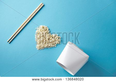 Side view I love wok takeaway noodles presentation with chopsticks, blank box and dry pasta in heart shape isolated on blue
