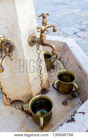 The fountain with the cups for washing hands before prayer in front of the Western Wall in Jerusalem. Travel to Israel .