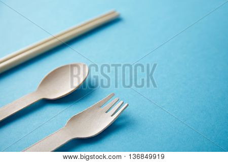 Different type of kitchen utencils for takeaway: asian chopsticks, spoon or fork made from recycled paper or wood, eco friendly, closeup isolated on turquoise