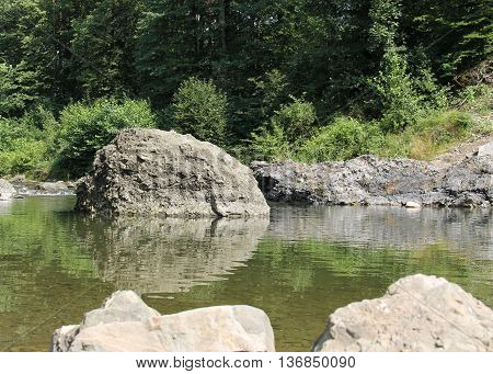 big rock in the river reflecting in the water surface
