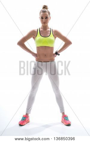 Portrait of pretty confident fit girl is standing with arms akimbo. She is looking forward with aspiration. Isolated